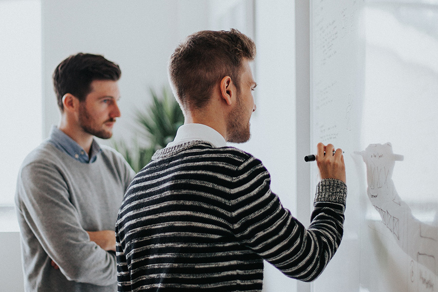 Two young men writing on a white board