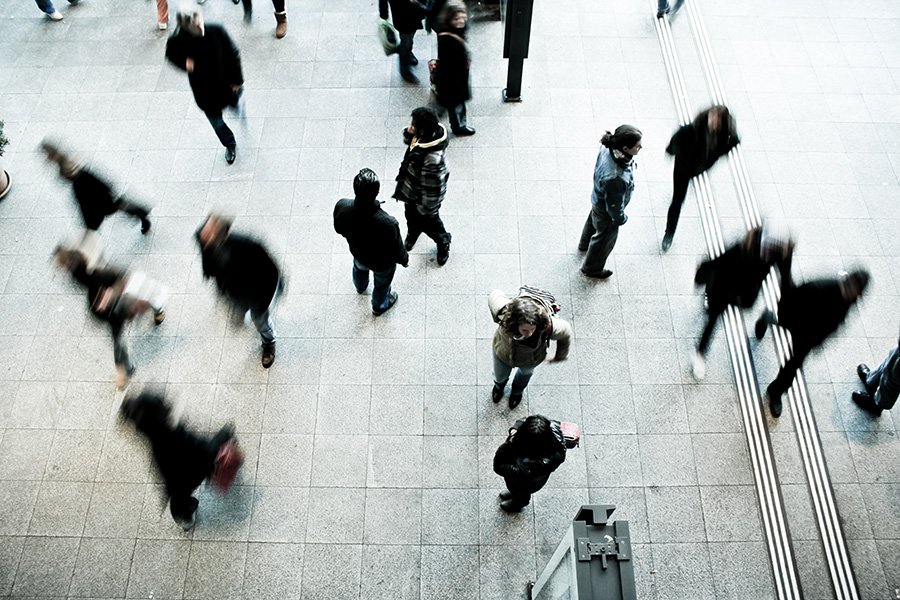 Various people walking on a concrete ground